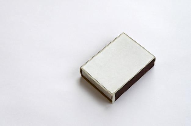 Scatola di fiammiferi di cartone chiusa sulla fine bianca della priorità bassa in su
