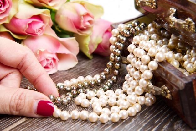 Scatola di gioielli con gioielli con rose rosa