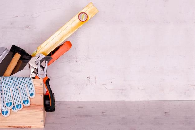 Scatola di legno con strumenti di costruzione su uno sfondo di cemento chiaro. messa a fuoco selettiva.