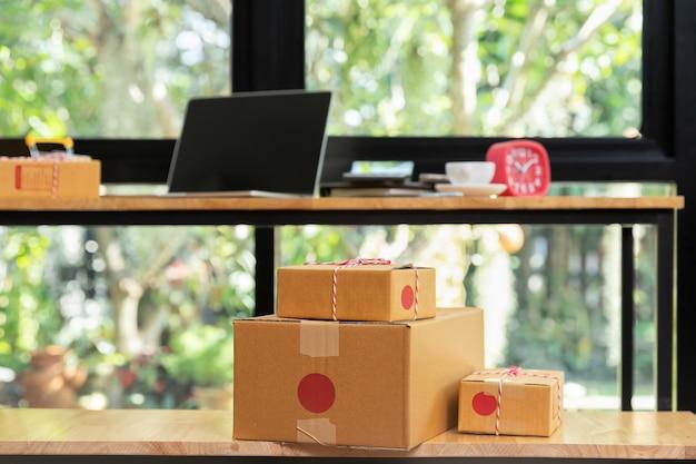 Scatola di pacchi di cartone e laptop sulla scrivania per la vendita online.