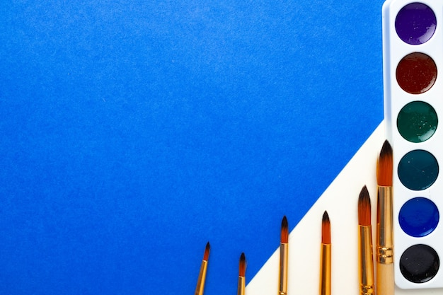 Scatola di pittura ad acquerello e set di pennelli su vista dall'alto di sfondo blu e bianco