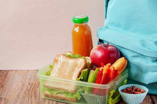 Scatola di pranzo con cibo appetitoso e zaino sul tavolo di legno.