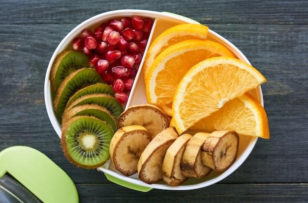 Scatola di pranzo con varie frutta fresche su legno