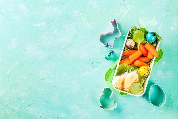 Scatola di pranzo per colazione creativa per bambini per pasqua, panini con formaggio, verdure fresche - cetrioli, carote, spinaci, uova di quaglia colorate. tavolo azzurro, copia spazio vista dall'alto