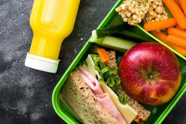 Scatola di pranzo sano della scuola con il panino, le verdure, la frutta e il succo su pietra nera