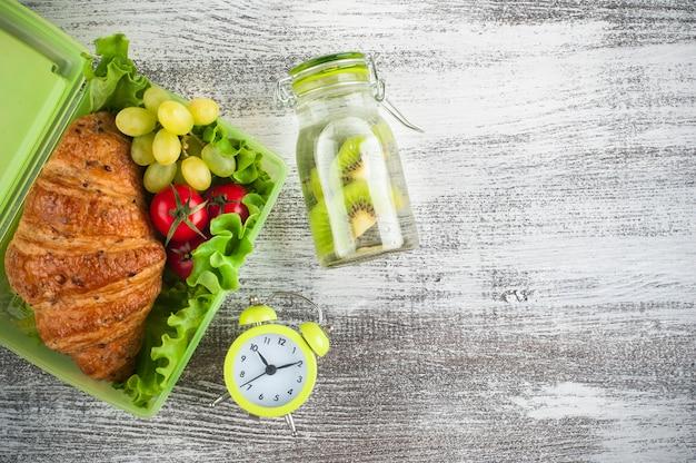 Scatola di pranzo verde con spuntino e un orologio