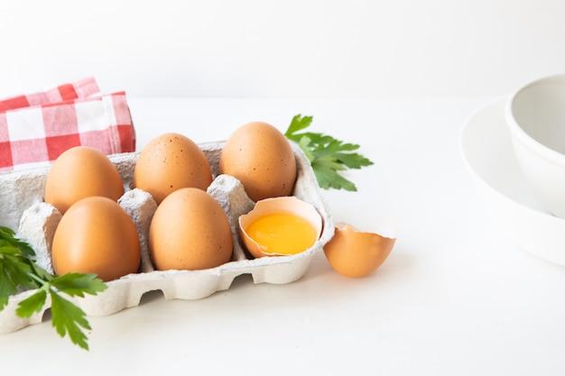 Scatola di uova sul tavolo bianco, prezzemolo e asciugatutto con capsula bianca