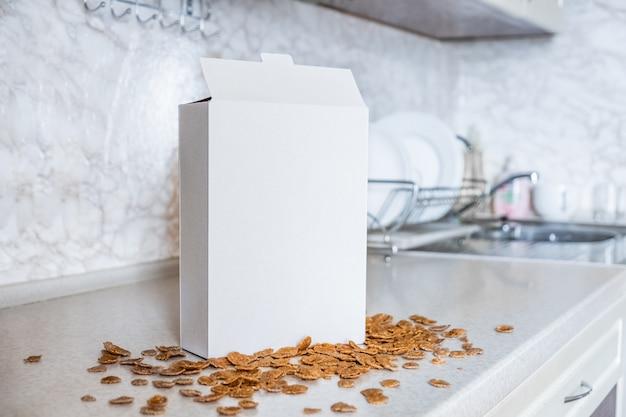 Scatola generica di cereali sul tavolo della cucina. pacchetto bianco della prima colazione pronta nella superficie domestica