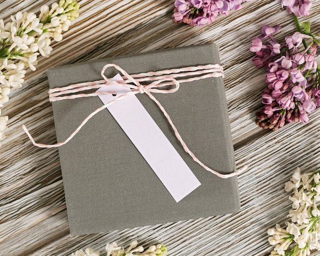 Scatola grigia con regalo su legno, fiori freschi lilla intorno. concetto di vacanza. vista dall'alto.