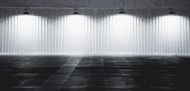 Scatola luminosa con la piattaforma di metallo della parete sopra con i riflettori, lampade che appendono sul fondo della parete