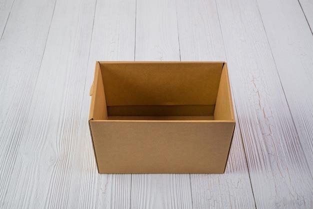 Scatola o vassoio di cartone marrone del pacchetto vuoto sulla tavola di legno luminosa con lo spazio della copia.
