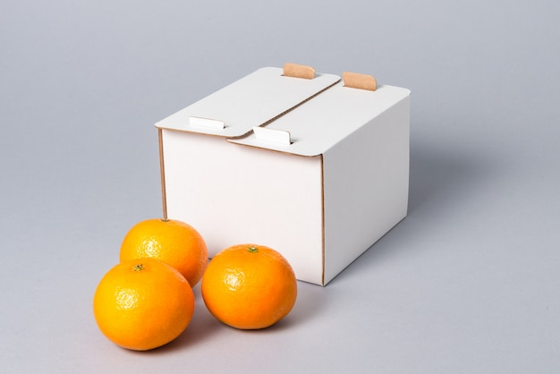 Scatola per dolci bianca del cartone con la copertura con i frutti, su fondo grigio
