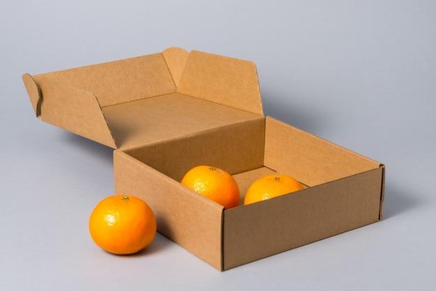 Scatola per dolci del cartone di brown con la copertura con i frutti, su fondo grigio