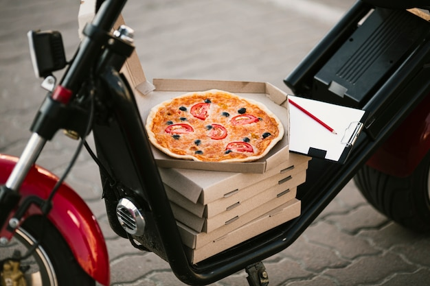 Scatola per pizza aperta sulla consegna moto