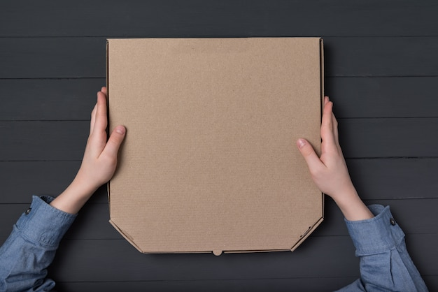 Scatola per pizza nelle mani dei bambini. sfondo nero. vista dall'alto. copia spazio.