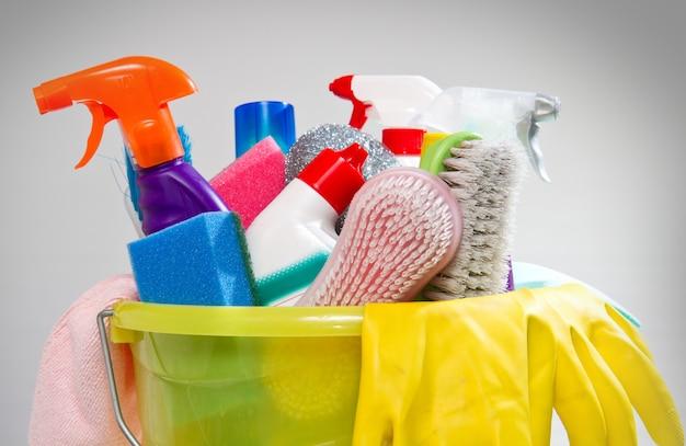Scatola piena di prodotti per la pulizia e guanti isolati su bianco