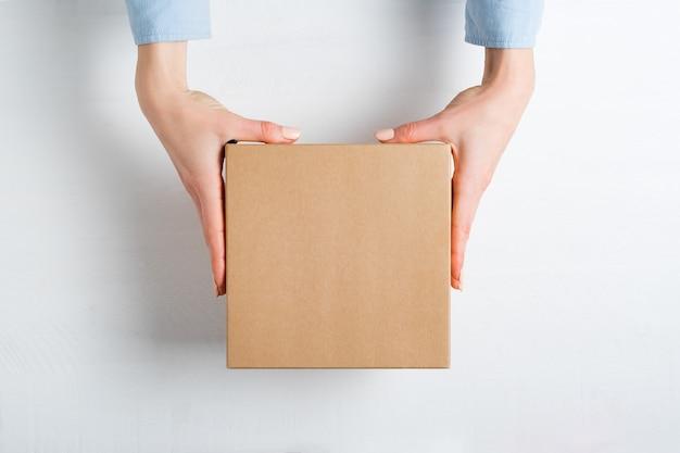 Scatola quadrata di cartone in mani femminili, vista dall'alto,