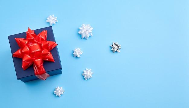 Scatola quadrata regalo di cartone blu scuro, fiocco rosso, nastri su sfondo blu