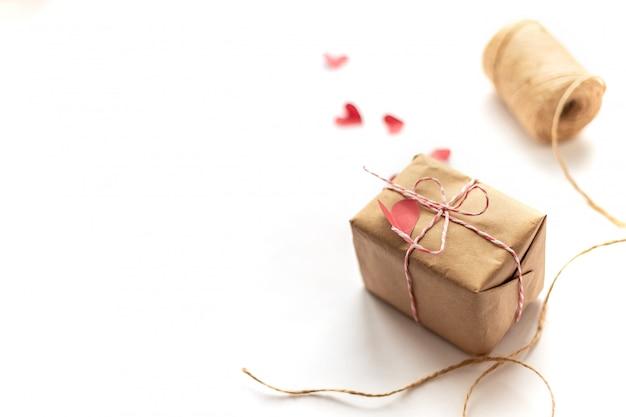 Scatola regalo artigianale che lega l'arco con corda di canapa su cuori bianchi di carta rossa con messa a fuoco selezionata