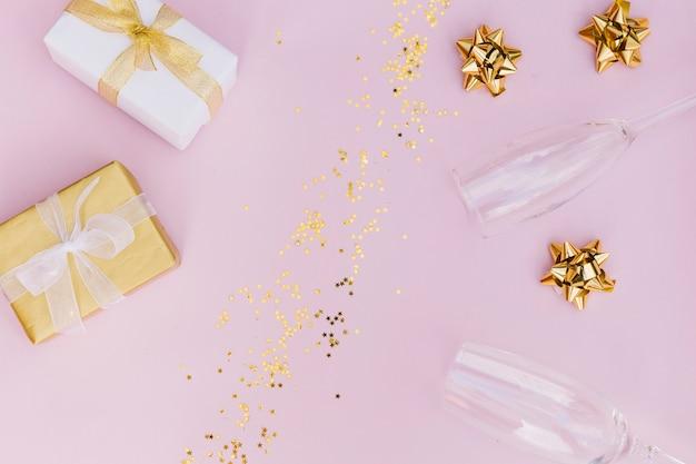 Scatola regalo avvolta con fiocco; coriandoli dorati; arco e bicchieri di champagne su sfondo rosa