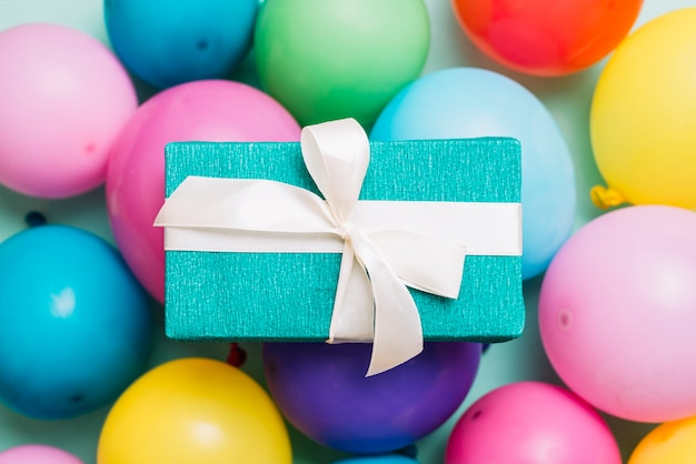 Scatola regalo avvolto legato con fiocco di nastro bianco su palloncini colorati