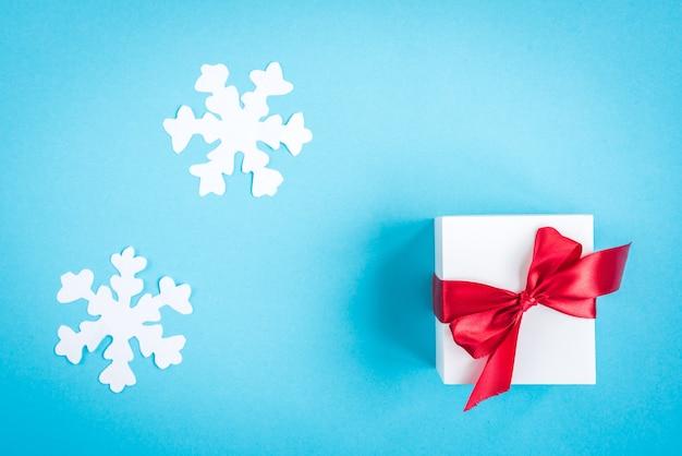Scatola regalo bianca con fiocco rosso e fiocchi di neve di carta sul blu con fiocchi di neve di carta.