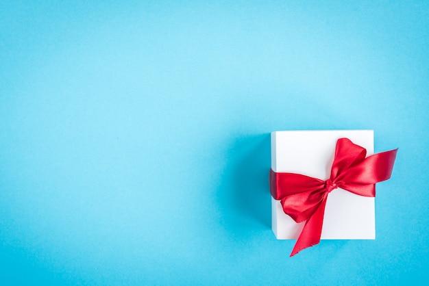 Scatola regalo bianca con fiocco rosso su blu con fiocchi di neve di carta.