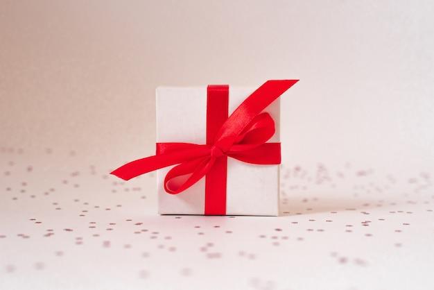 Scatola regalo bianca con nastro di raso rosso e fiocco e stelle su un bianco