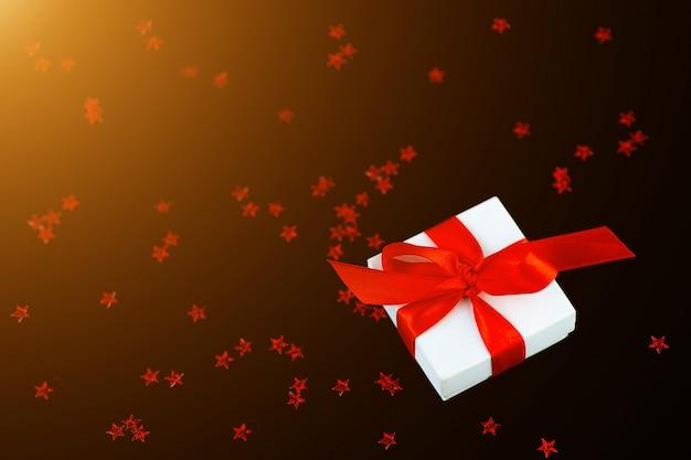 Scatola regalo bianca con un nastro rosso e uno scattering di stelle su sfondo nero.
