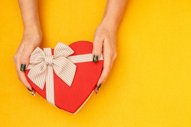 Scatola regalo biodegradabile in cartone a forma di cuore nelle mani delle donne