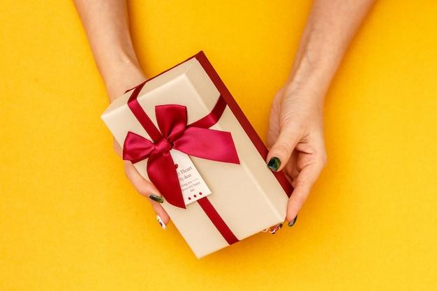 Scatola regalo biodegradabile in cartone nelle mani delle donne su giallo