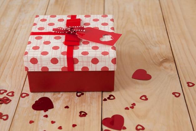 Scatola regalo circondata con decorazione cuore rosso