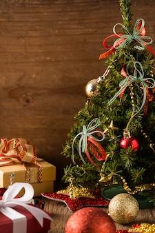 Scatola regalo con albero di natale su fondo in legno