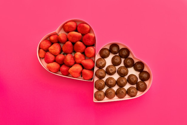 Scatola regalo cuore rosa per san valentino su uno sfondo rosa con fragole e cioccolato.