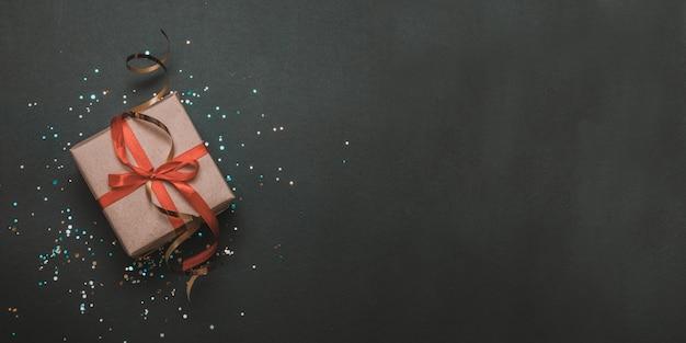 Scatola regalo di compleanno con nastro rosso e coriandoli oro su uno sfondo scuro contrasto