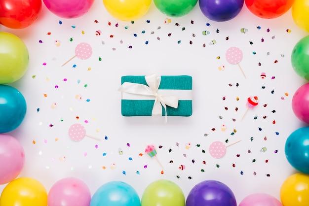 Scatola regalo di compleanno decorata con coriandoli; puntello e palloncini su sfondo bianco