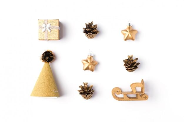 Scatola regalo di natale con decorazioni in oro, palline, stelle e coni su fondo bianco