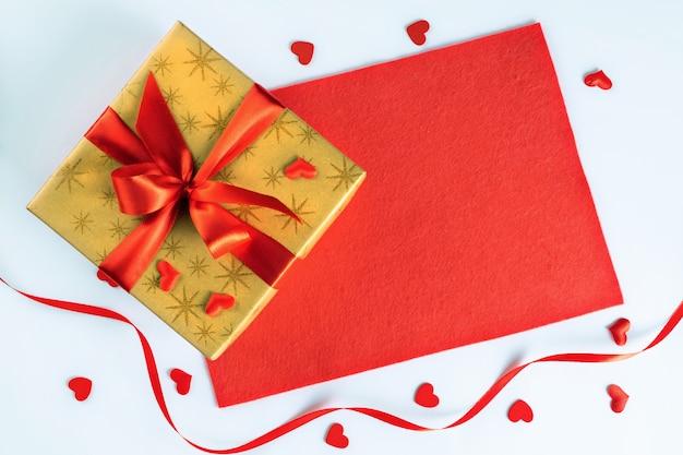 Scatola regalo dorata con nastro rosso su tessuto e cuoricini per san valentino