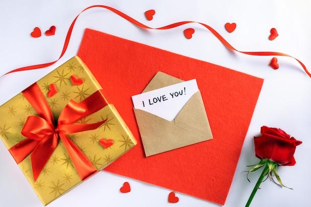 Scatola regalo dorata con nastro rosso su tessuto per san valentino