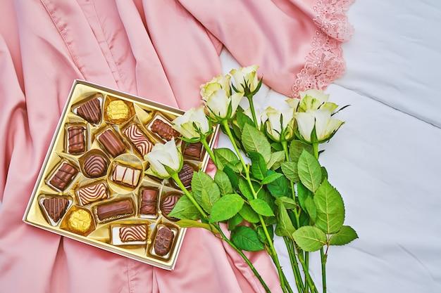 Scatola regalo dorata di cioccolato assortito su seta rosa con bouquet bianco di rosa