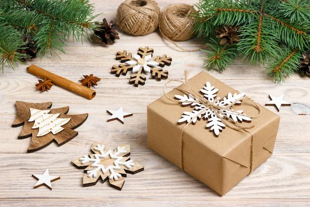 Scatola regalo in carta artigianale con decorazioni natalizie, spago, concetto, vista dall'alto sulla superficie del tavolo in legno, ornamenti natalizi e regali bordo con fiocchi di neve e stelle
