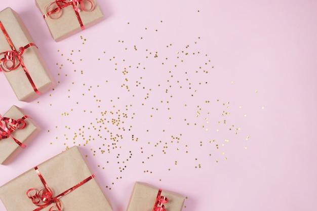 Scatola regalo o presente con paillettes stelle dorate su sfondo rosa.