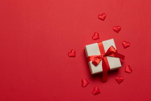 Scatola regalo o regalo con fiocco in nastro rosso e forma d'amore sul tavolo rosso. composizione di tendenza per compleanno, festa della mamma o matrimonio.