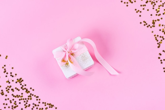 Scatola regalo o regalo con stelle di coriandoli e nastro rosa su colore rosa pastello. stile piatto laico.