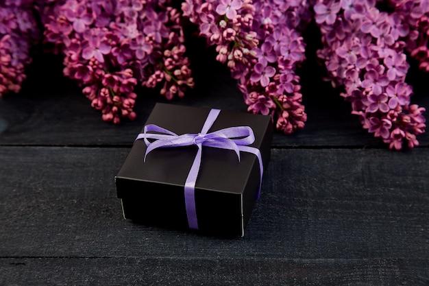 Scatola regalo piccola nera avvolta da un nastro viola con lilla naturale