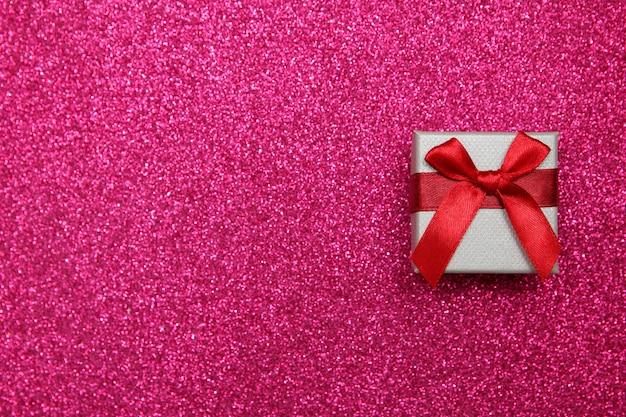 Scatola regalo rosa su sfondo rosa scintillante.