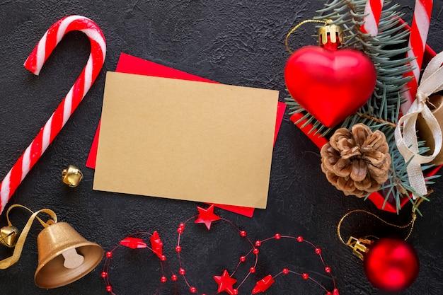 Scatola regalo rossa con un giocattolo di natale a forma di cuore, una campana d'oro, rami di abete, caramelle di natale, ghirlanda e carta per testo di congratulazioni