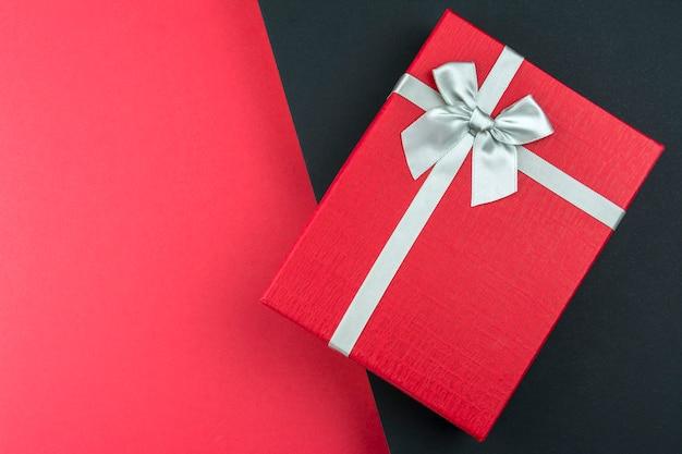 Scatola regalo rosso con fiocco su sfondo nero e rosso