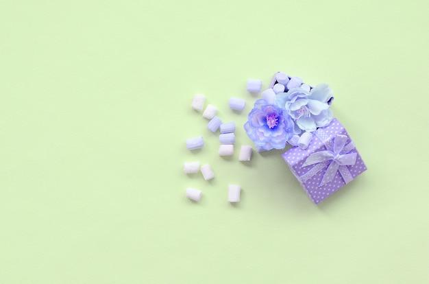 Scatola regalo viola fiorita cosparsa di marshmallow su lime