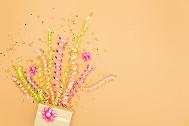 Scatola regalo yelow con vari coriandoli, stelle filanti, trombette e decorazioni su uno sfondo arancione.